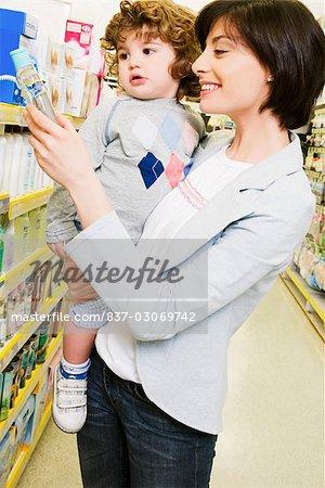 Femme portant son fils et en choisissant une huile pour bébé dans un supermarché
