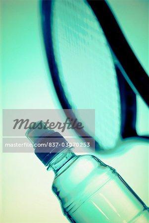 Gros plan d'une bouteille d'eau et une raquette de tennis