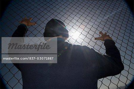 Prisonnier accroché à une clôture grillagée
