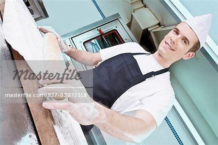 Chef, rouler la pâte avec un rouleau à pâtisserie