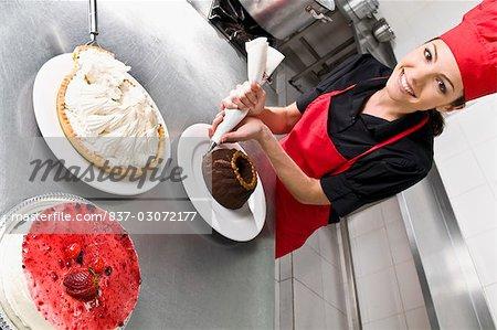 Female chef icing a cake