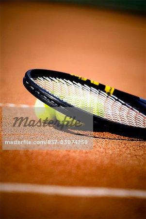 Gros plan d'une raquette de tennis et balles de tennis dans une Cour