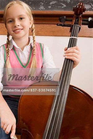 Schulmädchen spielt eine Violine in einem Klassenzimmer