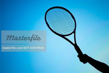 Gros plan de la main d'une personne détenant une raquette de tennis
