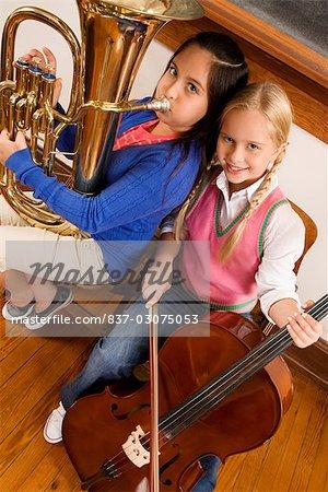 Porträt von zwei Mädchen spielen Violine und Tuba in einer Klasse