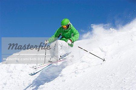 Homme en vert ski hors piste.