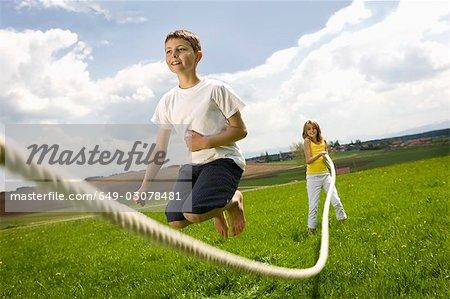 Enfants sautent au lasso dans campagne