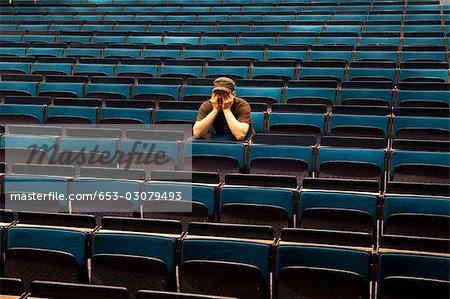 Ein Mann sitzt in einem Hörsaal, Hände, Augen abdecken
