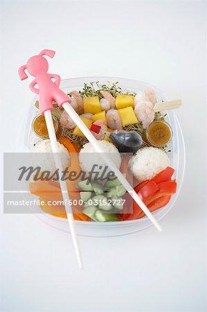 Brochettes de crevettes avec du riz et des légumes dans le récipient