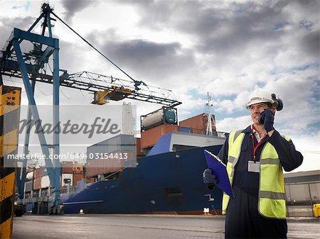 Port travailleur devant navire chargé