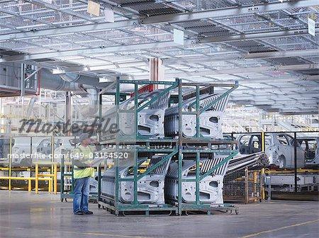 Travailleur d'usine de voiture avec les portières