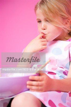 Gros plan d'une jeune fille tenant un bol allant au four, sucer son doigt