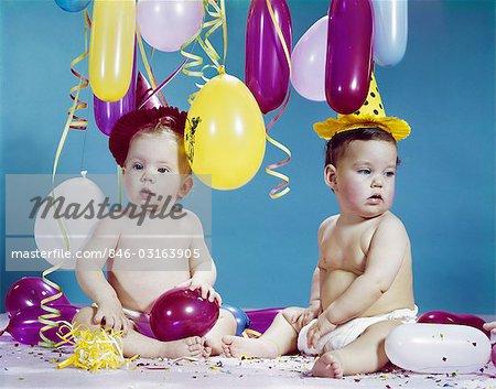 1960ER JAHRE ZWEI BABYS TRAGEN PARTYHÜTEN MIT LUFTBALLONS LUFTSCHLANGEN KONFETTI