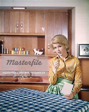ANNÉES 1960 GRAVE MÉNAGÈRE BLONDE FAIRE SHOPPING LISTE AT CUISINE TABLE