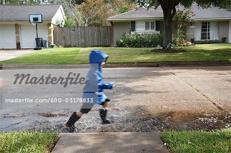 Garçon marchant dans des flaques d'eau sur la rue