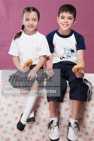 Garçon et sa sœur holding donuts et souriant