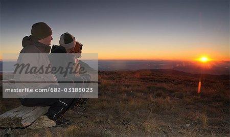 Trois randonneurs vêtus de vêtements chauds, regarder le lever du soleil sur l'horizon, pic de la cathédrale, UKhahlamba National parc du Drakensberg, Province du KwaZulu-Natal, Afrique du Sud.