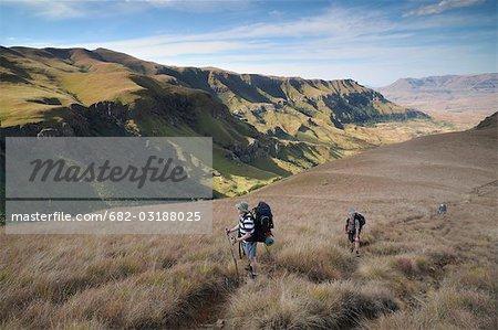 Trois randonneurs marchant vers le haut vers la petite Berg dans la Section de pic de la cathédrale du parc de la National Ukhahlamba Drakensberg, Province du KwaZulu-Natal, Afrique du Sud