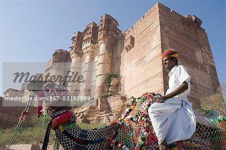 Homme monté sur un chameau devant un fort Mehrangarh Fort, Jodhpur, Rajasthan, Inde