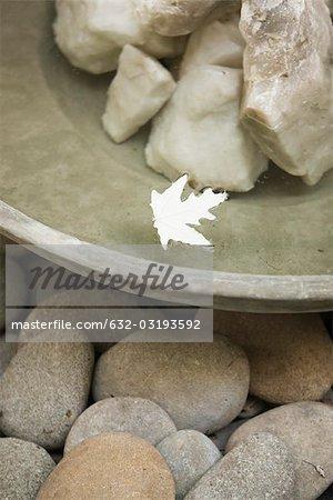 Feuille flottant dans l'eau qui coule sur les rochers dans le bol de la fontaine