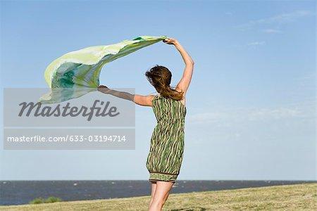 Femme debout à l'extérieur, brandissant le châle en vent, pleine longueur