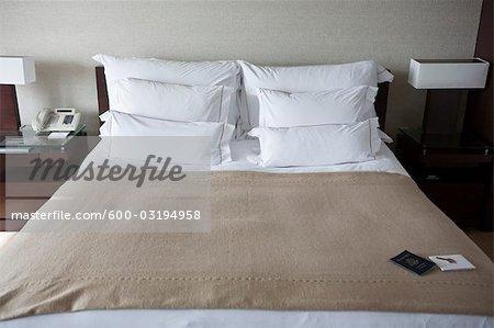 Clé et passeport sur lit d'hôtel