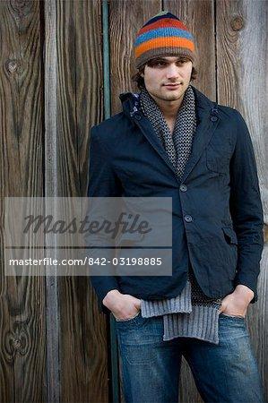 Junger Mann in warme Kleidung stehen außerhalb der hölzernen Gebäude
