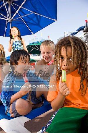 Groupe multiethnique d'enfants manger des sucettes glacées