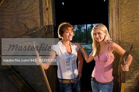 Mère et fille adolescente debout devant l'étable