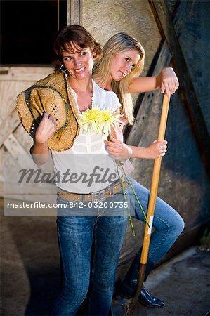 Femmes portant des jeans avec chapeau de cow-boy dans l'écurie