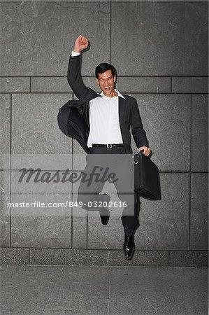 homme d'affaires détenant des porte-documents, sautant avec bras levé