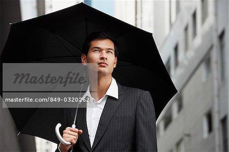 homme d'affaires tenir parapluie, en levant