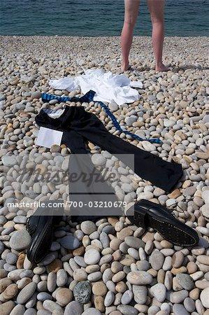 Homme d'affaires et des vêtements épars sur la plage