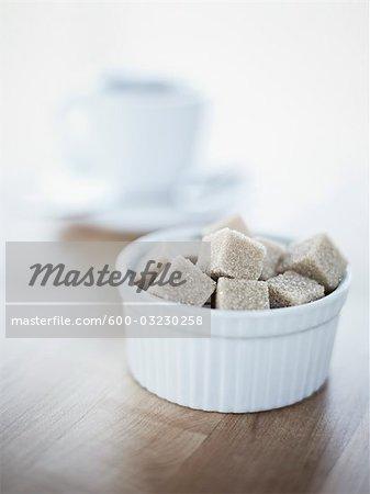 Bol de Cubes de sucre brut, tasse de café en arrière-plan