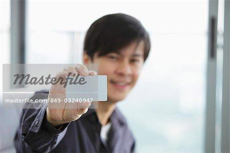 Jeune homme tenant une carte de crédit