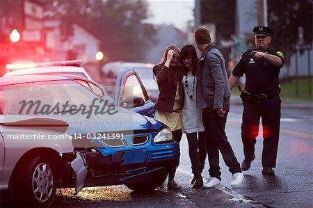 Jeunes et policier sur les lieux de l'accident de voiture
