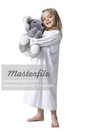 Jeune fille en nuisette holding jouet en peluche ours de koala