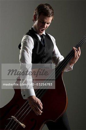 Junger Mann spielen Kontrabass wie eine Gitarre, Studioaufnahme