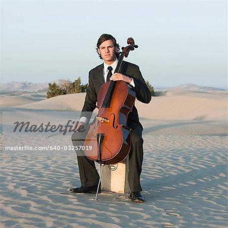USA, Utah, Little Sahara, Porträt des jungen Mannes mit Cello in der Wüste