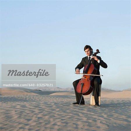 USA, Utah, Little Sahara, junger Mann mit Cello in der Wüste
