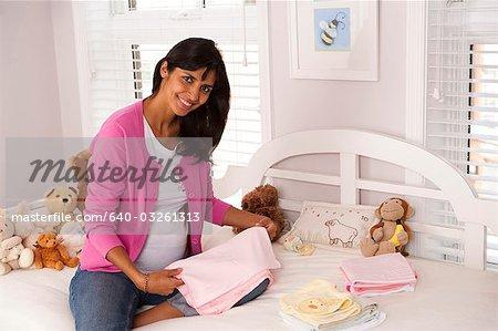 Femme enceinte avec les vêtements de bébé et animaux en peluche
