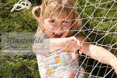 Girl in swimsuit playing in hammock