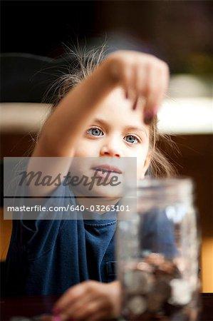 Junges Mädchen zählen Münzen aus Glas