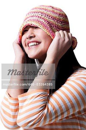Adolescente souriante et mettre sur un chapeau