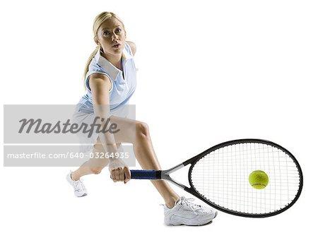 Close-up of tennis player hitting ball
