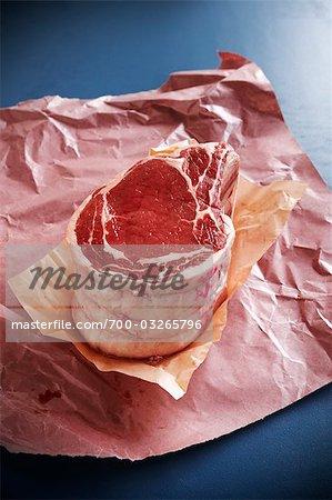 Côte de boeuf cru sur du papier de boucherie