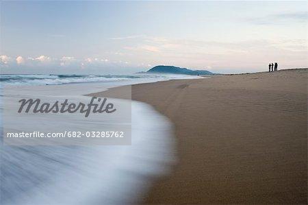 Touristes au bord du rivage à l'aube, plage de l'estuaire, St Lucia, Kwazulu-Natal, Afrique du Sud