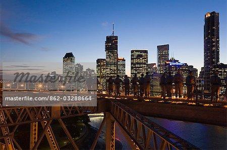 Un groupe d'alpinistes sur le pont histoire de Brisbane est silhouetté sur les toits de la ville illuminée. Le Story Bridge aventure grimper a ouvert en 2005 et est l'un de seulement quatre de ces expériences dans le monde.