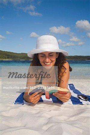 Une femme se détend sur la plage de sable blanc du lac McKenzie - un endroit populaire pour la baignade sur l'île de Fraser World Heritage Listed.