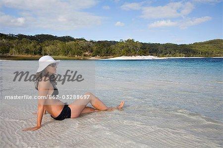 Une femme donne sur les eaux claires et la plage de sable blanc du lac Mckenzie sur l'île de Fraser.